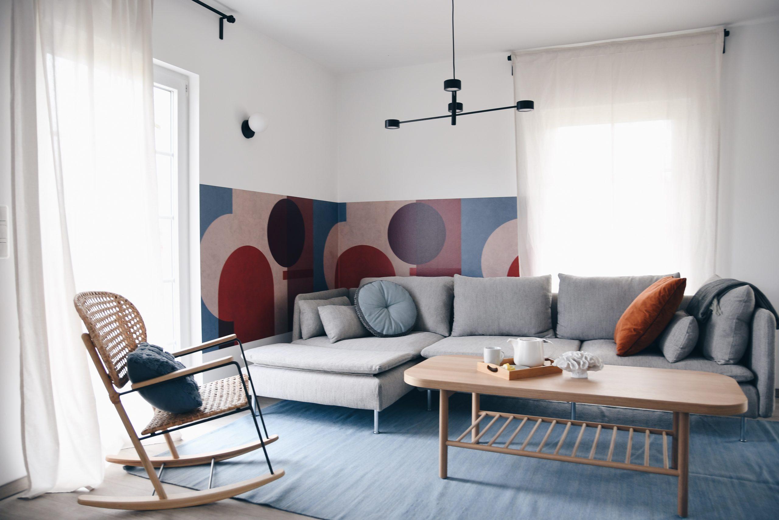 Wohnzimmer-Design mit bunter Tapete und gemütlichem Sofa und Schaukelstuhl